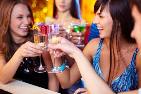 Portret van vrolijke vrienden roosteren op verjaardagsfeestje met focus op lachend meisje Stockfoto