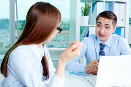 Image of two white collar workers during discussion of business ideas at meeting photo