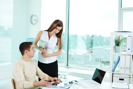 Image of confident businessman with ipad tablet looking at pretty colleague near by photo