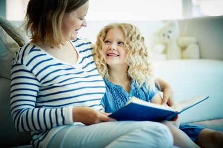 kids reading book: Portrait of cute girl listening to her mother telling an interesting story at home