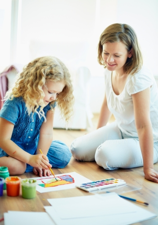 Portrait of cute girl painting with colorful gouache with her mother near by photo