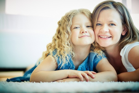 Portrait of happy woman and her daughter lying on the floor photo