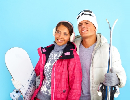 winterwear: Portrait of pretty girl and handsome man in winterwear holding snowboard and skis