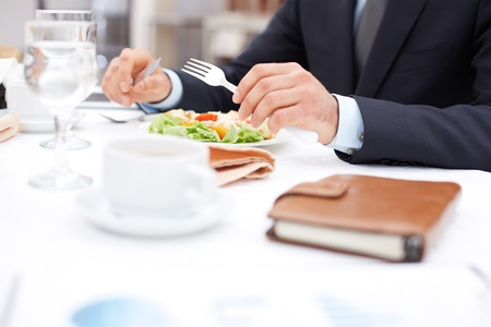 dinner: Close-up of businessman hands holding knife and fork over vegetable salad during business lunch Stock Photo