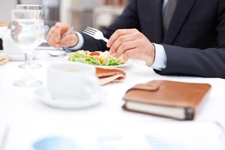 Close-up de mains d'affaires tenant un couteau et une fourchette sur la salade de légumes au déjeuner d'affaires