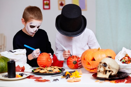 pumpkin carving: Photo of two eerie boys drawing on pumpkins at Halloween table
