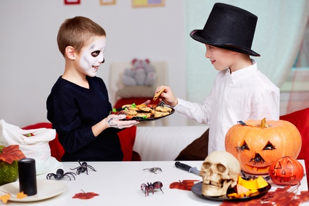 antichrist: Photo of two eerie boy offering cookies to his twin brother on Halloween day Stock Photo