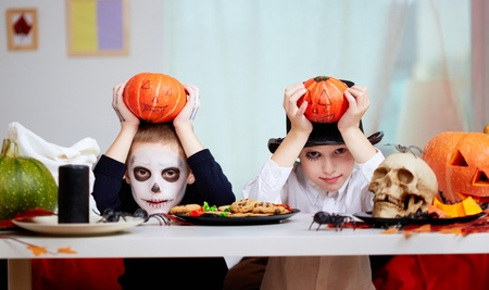 antichrist: Photo of twin eerie boys holding Halloween pumpkins over their heads and looking at camera