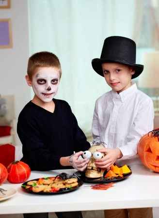 antichrist: Photo of twin boys holding spooky eyes just in skull eye-sockets and looking at camera Stock Photo