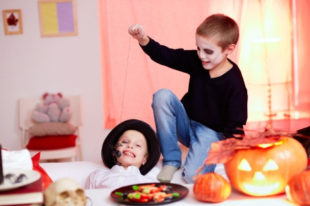 antichrist: Photo of evil boy scaring his twin brother with spider on Halloween