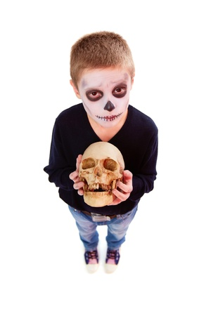 antichrist: Photo of eerie boy with human skull looking at camera