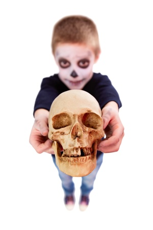 death head holding: Photo of eerie boy with human skull showing it to camera