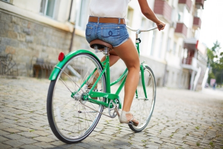 bicyclists: Close-up of rear view of a pretty woman on bicycle
