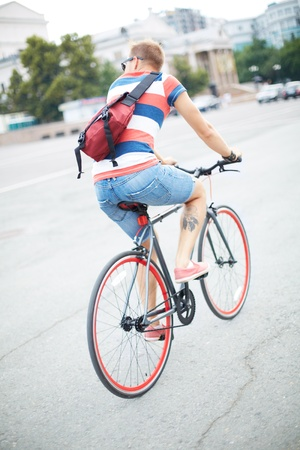 back roads: Back view of youngguy riding bicycle in the city center Stock Photo