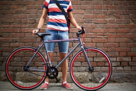 レンガの壁の自転車を持つ男のクローズ アップ