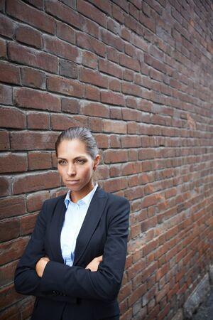 spiteful: Image of angry businesswoman walking along brick wall Stock Photo