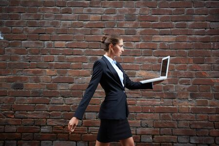 Image of confident businesswoman with laptop walking along brick wall photo