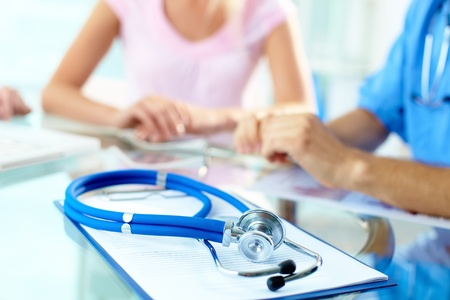 focus group: Close-up of stethoscope and paper on background of doctor and patient hands Stock Photo