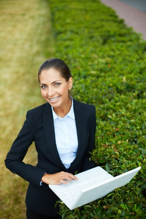 Image of young businesswoman with laptop looking at camera while networking in park photo