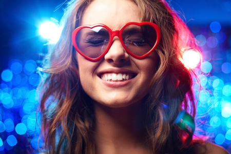 heartshaped: Girl with heart-shaped glasses and closed eyes smiling
