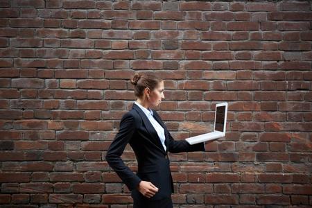 Image of serious businesswoman with laptop walking along brick wall photo
