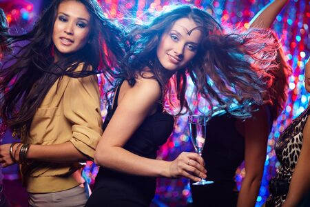 Young woman looking at camera while dancing at nightclub among her friends photo