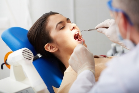 Close-up of girl with open mouth during oral checkup at the dentist�s photo