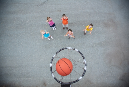 Image of happy friends playing basketball on sports ground photo