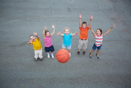Image of happy friends playing basketball on sports ground Banco de Imagens