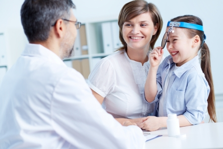clinician: Cute girl and her mother consulting with the doctor in hospital Stock Photo