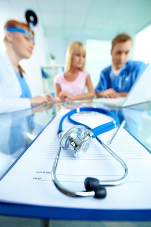 Close-up of stethoscope and paper with pen on background of doctors and patient working with laptop photo