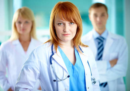 clinician: Portrait of pretty clinician in white coat looking at camera