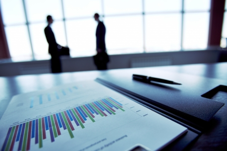 business review: Close-up of a financial report with the silhouettes of business people in the background Stock Photo