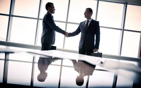 Silhouettes de deux hommes d'affaires debout près de la fenêtre et poignées de main