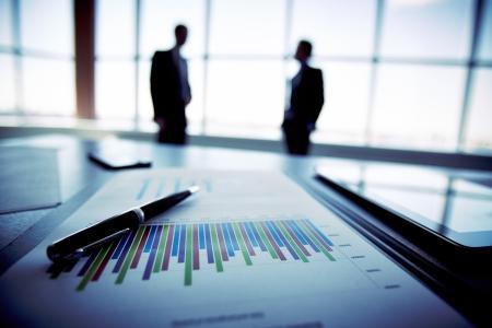 バック グラウンドでのビジネス人々 のシルエットと財務報告のクローズ アップ 写真素材