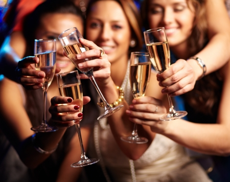 Group of partying girls clinking flutes with sparkling wine