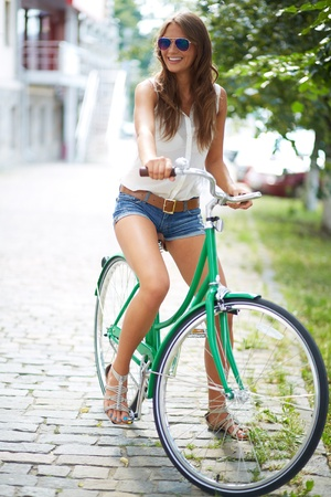 recreational vehicle: Portrait of a pretty woman on bicycle in the park Stock Photo