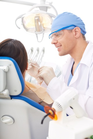 Mature dentist giving oral checkup to young girl photo