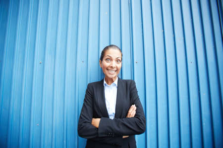 Image of happy businesswoman standing by blue wall and looking at camera   Stock Photo - 21306952