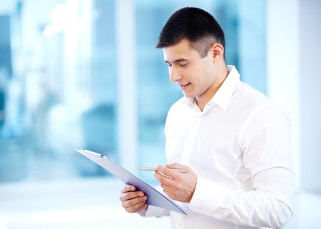 Portrait of cheerful businessman reading his notes photo