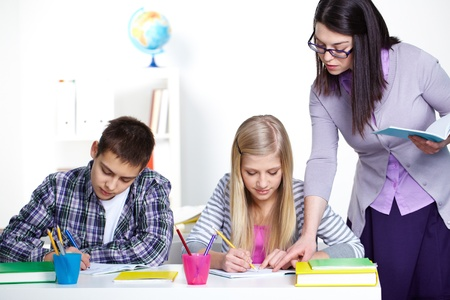 Portrait of teenage lad and girl writing somethinig during lesson while teacher checking their notes