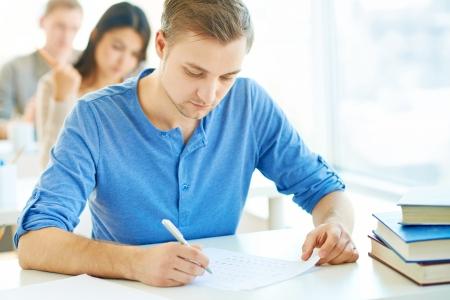 handsome student: Retrato del estudiante guapo llevar a cabo la prueba en clase con compa?s de grupo en el fondo Foto de archivo