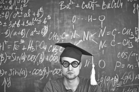 Black-and-white image of student in graduation hat and eyeglasses looking at camera on background of chalkboard photo