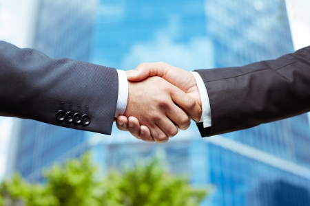trust: Close-up of business people handshaking on background of modern building