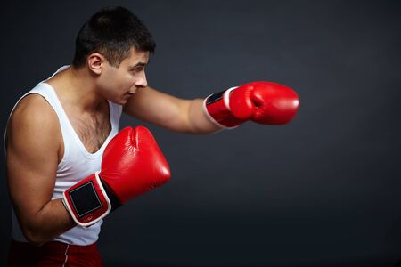 kick boxer: Portrait of young man in red boxing gloves fighting in isolation
