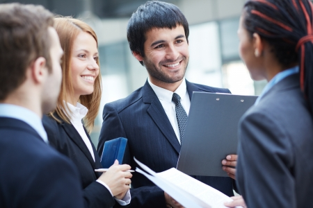 conversation: Group of business partners planning work with focus on smiling man Stock Photo
