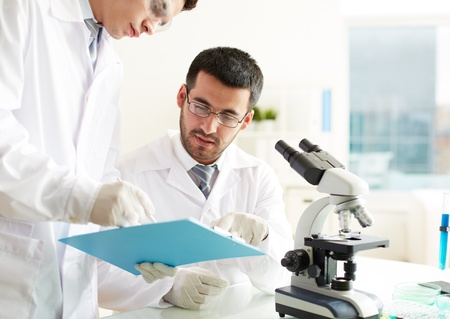 Two clinicians discussing medical document in laboratory