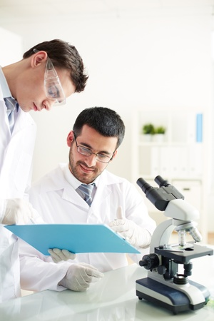 Two clinicians discussing medical document in laboratory photo