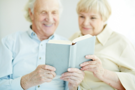 Senior couple holding and reading book together photo