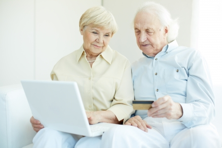 Senior couple with credit card and laptop during shopping through Internet photo